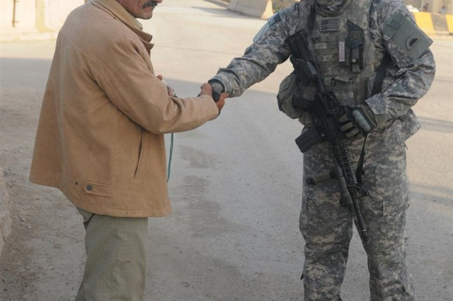 Pfc. Alexander J. Miller, an armored infantry cavalry scout with A Troop, 1st Squadron, 82nd Cavalry Regiment, 41st Infantry Brigade Combat Team, 13th Sustainment Command (Expeditionary) and a Camby, Ore., native, shakes hands with a local national March 8, at entry control point 13 at Victory Base Complex, Iraq. All local nationals must pass through a tiered screening process before they are allowed to enter the base.