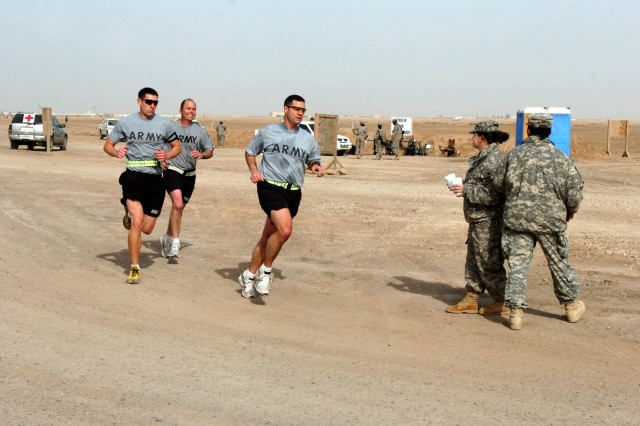 Soldiers and civilians pass a water point while participating in the Contingency Operating Location Sykes Half Marathon Wounded Warrior Project Fundraiser, at COL Sykes, Tal Afar, Iraq, Feb. 24, hosted by the Soldiers of the Tennessee Army National Guard's 1st Squadron, 230th Air Cavalry Squadron, Troop F, Task Force Desperado. The 13.1 mile race raised $4,000 for the Wounded Warrior Project (WWP). (Photo by: Staff Sgt. Mike Alberts  25th Combat Aviation Brigade Public Affairs)