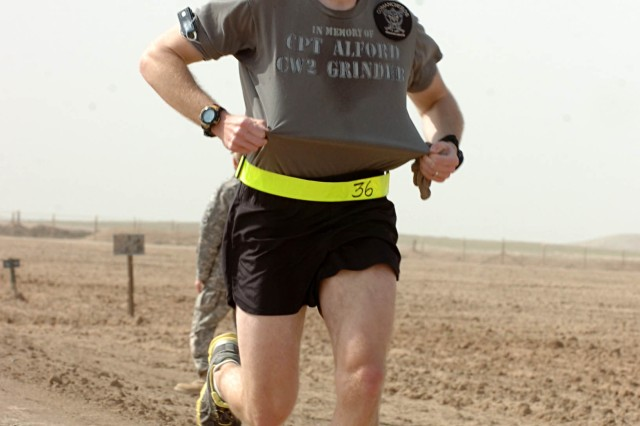 Chief Warrant Officer Two Jameson Quaine, AH-64D Apache pilot, Company C., 2nd Squadron, 159th Attack Reconnaissance Battalion, places first in the Contingency Operating Location Sykes Half Marathon Wounded Warrior Project Fundraiser, at COL Sykes, Tal Afar, Iraq, Feb. 24. Chief Quaine displayed a T-shirt he and others in his unit created in memory of Capt. Marcus Alford of Knoxville, Tenn., and Chief Warrant Officer Two Billie Jean Grinder, of Gallatin, Tenn., killed in an OH-58D helicopter accident, Feb. 21. (Photo by: Staff Sgt. Mike Alberts  25th Combat Aviation Brigade Public Affairs)
