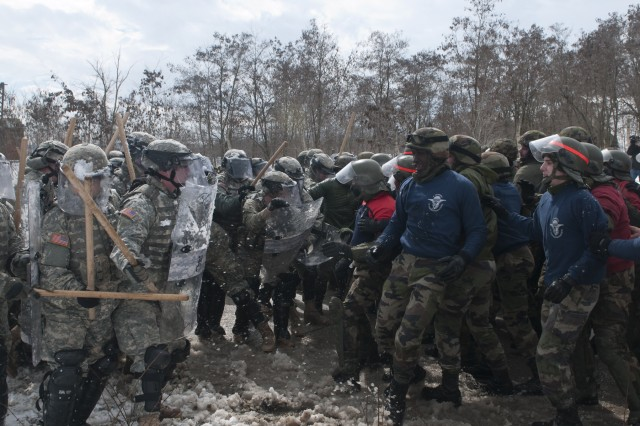 """U.S. KFOR Soldiers of Bravo and Charlie Company, 231st Maneuver Task Force of Multi-National Battle Group-East hold strong as """"rioters,"""" played by other KFOR Soldiers form the French and Swiss Armies, give them resistance, during a recent simulated riot-control exercise March 11 at Camp Vrelo, Kosovo."""