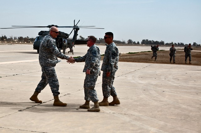 CAMP TAJI, Iraq - Shortly after arriving on Taji airfield, Gen. Ray Odierno (left), from Rockaway, N.J., commanding general, U.S. Forces - Iraq, shakes the hand of Col. Douglas Gabram (center), from Cleveland, Ohio, commander, 1st Air Cavalry Brigade, 1st Cavalry Division, U.S. Division-Center, as Command Sgt. Maj. Glen Vela (right), from Dallas, brigade command sergeant major, 1st ACB,  looks on, March 9. Odierno was visiting the 1st ACB troopers to hear about their lessons learned during the deployment and to congratulate them as they begin their transition from Iraq to the U.S.
