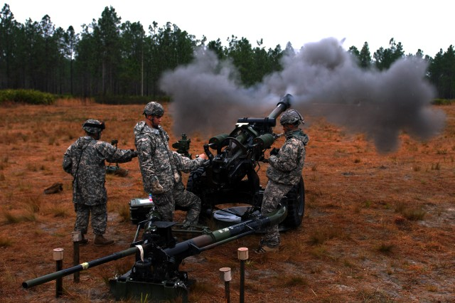 CAMP BLANDING, Fla--(From left) Sgt. Sandro Lucas, gun chief; Pfc. Ralph Jansen, Number Two; and Spc. Christopher Velasquez, assistant gunner stand clear as Sgt. Erwin Dominguez, gunner, fires a round from an M119A2 howitzer on Camp Blanding, Fla., March 12. The Soldiers are members of the New York Army National Guard's A Battery, 1st Battalion, 258th Field Artillery Regiment from New Windsor, N.Y.