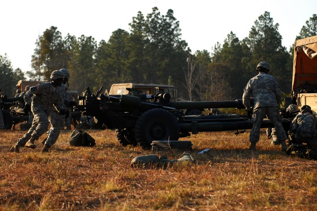 CAMP BLANDING, Fla--Sgt. Frantz Sylvain (left), the Gun Eight team gunner for Battery B, 1st Battalion, 258th Field Artillery Regiment, races to help his crew set up their M119A2 howitzer at a firing point on Camp Blanding, Florida March 10. During an emplacement drill, gun crews have eight minutes to get their howitzers into firing position.