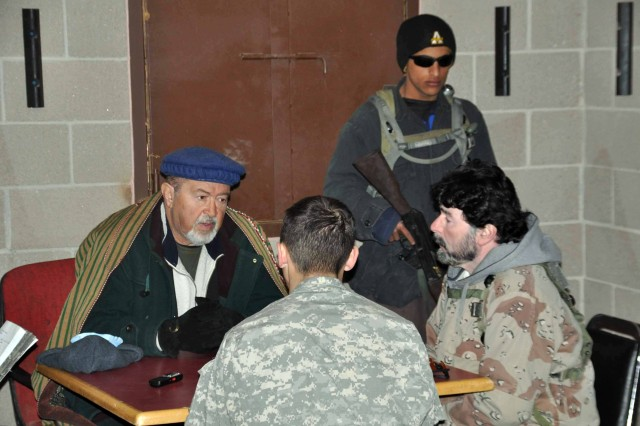 FORT CARSON, Colo.-(from left) Ahmad Shah Alam, portraying a tribal leader during the training exercise, speaks to 2nd. Lt. Jason Bourque through a translator, Khalid Sadozai, about his towns needs, and warns of another town's hostile intent.