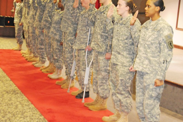 Twelve Fort Rucker Soldiers raise their right arms as they reenlist March 4 at the U.S. Army Aviation Center of Excellence Headquarters.
