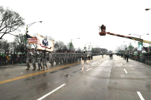 Soldiers from the Chicago Recruiting Battalion, proudly display the Army and American Flags, while marching in the 2010 Saint Patrick's Day Parade on Saturday, 12 March in Chicago, IL.  Sgt. 1st Class Clifton Davis, Glenview, IL Recruiting Company, West Addison Recruiting Station, calls cadence for his fellow Soldiers.  In the background are some of the over 200,000 spectators and one of the ABC 7 camera operators in a crane, whose station broadcast the event live.