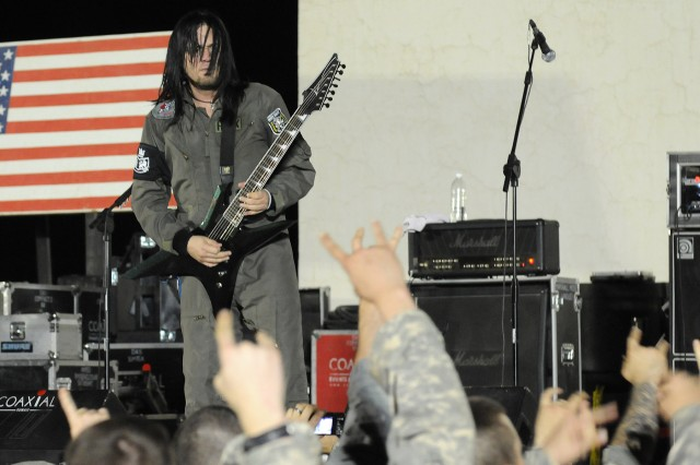 Five Finger Death Punch guitarist Jason Hook plays a guitar solo for cheering Soldiers during a concert March 5 at Contingency Operating Location Q-West, Iraq. (U.S. Army photo by Staff Sgt. Rob Strain, 15th Sustainment Brigade Public Affairs)