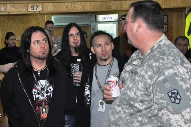 Col. Larry Phelps, the commander of the 15th Sustainment Brigade, explains the brigade's mission to members of the heavy metal band Five Finger Death Punch during a tour of Contingency Operating Location Q-West, Iraq, March 5. (U.S. Army photo by Staff Sgt. Rob Strain, 15th Sustainment Brigade Public Affairs)