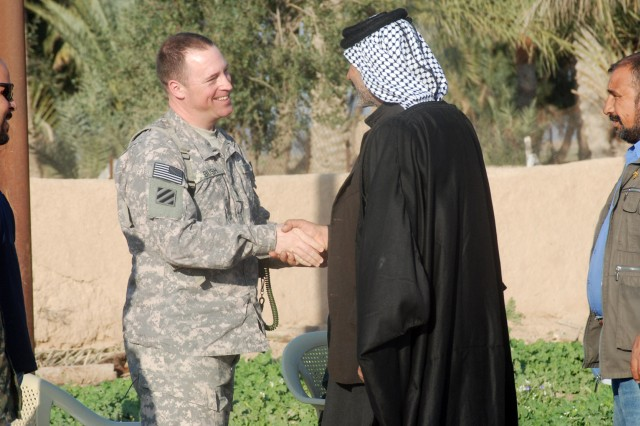 """Lt. Col Mike Bush greets the shaykh of the Katawi Tribe during a meeting in Wasit Province March 2. The shaykh bestowed the """"yashmagh,"""" the traditional headdress of Arabic tribesmen, and """"agal,"""" the black wool headband, to Bush. The highly-inclusive honor is usually kept within the tribe, and formal ceremonies to present the agal and yashmagh to """"outsiders"""" are rare."""