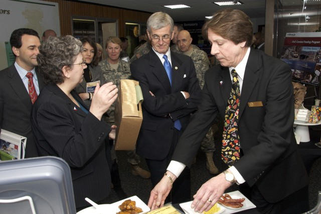 Department of Defense Combat Feeding Director Gerald Darsch (right) and team leader Kathy Evangelos demonstrate technology advances in food science for Secretary of the Army John McHugh March 15 at Fort Belvoir, Va.