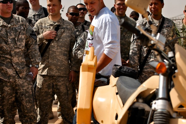 "CAMP TAJI, Iraq - During a visit with Soldiers from 1st Air Cavalry Brigade, 1st Cavalry Division, U.S. Division-Center, actor Theo Rossi (white shirt), a lead actor in the hit TV show ""Sons of Anarchy,"" looks at an Iraqi Army motorcycle March 15. Air cavalry Soldiers welcomed the actors with aircraft displays and a town hall meeting where the actors fielded questions from them."