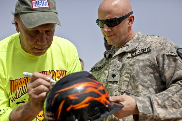 """CAMP TAJI, Iraq - Spc. Chris Bollingmo, from New Ulm, Minn., an AH-64D Apache attack helicopter crew chief in Company B, 615th Aviation Support Battalion, 1st Air Cavalry Brigade, 1st Cavalry Division, U.S. Division-Center, gets his helmet signed by Dayton Callie, a lead actor in the television show """"Sons of Anarchy,"""" March 15. Four cast members from the show visited 1st ACB Soldiers, getting a close look at their helicopters and signing autographs at a barbecue lunch."""