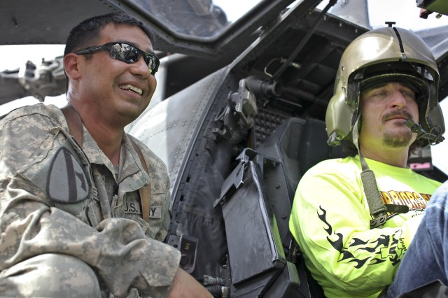 "CAMP TAJI, Iraq - While sitting in an AH-64D Apache attack helicopter March 15, Kim Coates talks with Chief Warrant Officer 3 Rolando Sanchez, an Apache maintenance test pilot in Company C, 1st Battalion, 227th Aviation Regiment, 1st Air Cavalry Brigade, 1st Cavalry Division, U.S. Division-Center, about some of the various controls and functions of the aircraft. Coates is a lead actor in the television show, ""Sons of Anarchy."" During a three-hour visit, 1st ACB Soldiers had an opportunity to talk with Coates and other actors from the show at a town hall meeting."