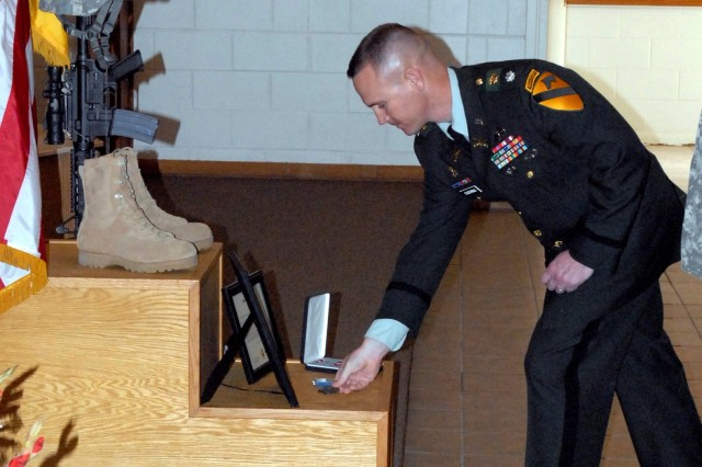 FORT HOOD, Texas-Lt. Col. John Cushing, commander of the 1st Squadron, 9th Cavalry Regiment, 4th Brigade Combat Team, 1st Cavalry Division, places a battalion coin of achievement on 1st Lt. Michael Thomas Jue's memorial during the remembrance ceremony at the Fort Hood Operation Iraqi Freedom Veteran's Chapel on March 15. Jue died March 2 after collapsing during morning physical fitness training.
