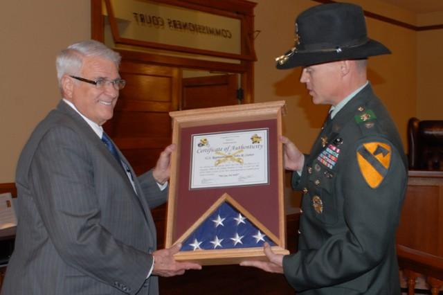 Congressman Dan Carter (left) accepts a flag from Lt. Col. Andy Shoffner, commander of 4th Squadron, 9th Cavalry Regiment, 2nd Brigade Combat Team, 1st Cavalry Division, during a ceremony in Williamson County. The flag was flown over the Squadron's headquarters during their most recent deployment to Kirkuk, Iraq.