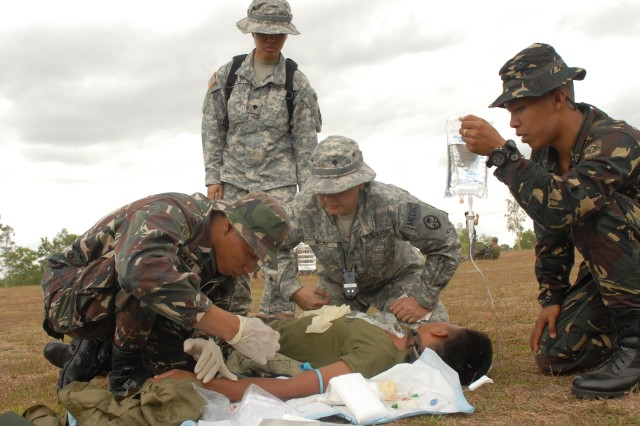 FT. RAMON MAGSAYSAY, LUZON, Republic of the Philippines (March 12, 2010) - U.S. Soldiers from the Guam Army National Guard Medical Detachment observe as 7th Infantry Division, Philippine Army soldiers administer an IV to a mock patient during a casualty evacuation exercise on the parade field here. The Philippine soldiers tested their newly-acquired basic medical skills after a three-day combat lifesaving course during the Balikatan 2010 Field Training Exercise.