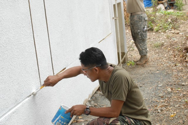 BARANGAY LABI, NUEVA ECIJA, LUZON, Republic of the Philippines (March 13, 2010) - Soldiers from the Philippine Army and the Guam Army National Guard paint the community health center here Mar. 13 during a community outreach program, part of the Balikatan 2010 Field Training Exercise.