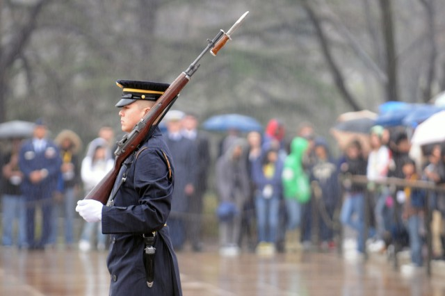 Watched by an audience that includes members of the Senate Youth Program, a Soldier guards the Tomb of the Unknowns at Arlington National Cemetery in Arlington, Va., on a rainy March 12. National Guard officers served as military mentors for the 104 high school students selected for a week in the nation's capital.