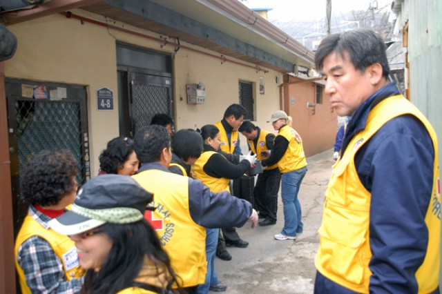Oh, Sea-chang, mayor of Dongducheon city, looks on as the volunteers from the American Red Cross and Korean Red Cross pass out charcoal bricks within the city to the elderly and poor March 6.