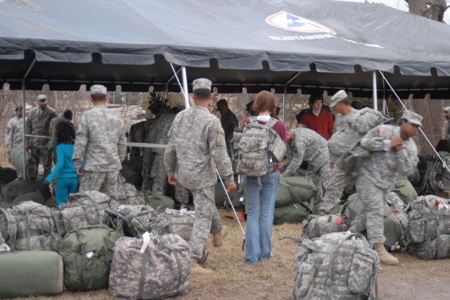 After the ceremony, 3d ESC Soldiers scoured through the mountain of baggage. (U.S. Army photo by Robert Stevenson)