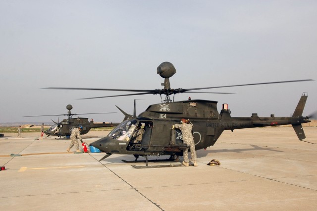 Soldiers from Troop E, 2nd Squadron, 6th Cavalry Regiment, Task Force Lightning Horse, re-fuel and re-stock an OH-58D Kiowa Warrior helicopter with hot fuel and ammunition at the Lightning Horse Forward Arming and Re-Fueling Point at Contingency Operating Site Warrior, near Kirkuk, Iraq, Feb. 14. (Photo by:  Sgt. 1st Class Tyrone C. Marshall  25th Combat Aviation Brigade Public Affairs).