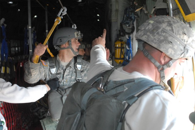 Airborne student, 2LT Charles Lesperance, left, gives other students the one-minute warning prior to his first jump.  Lesperance was the first student to jump with the T-11.