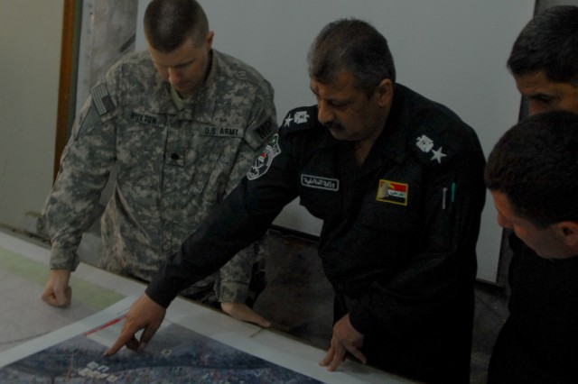 Iraqi Police Lt. Col. Awooda Abdal Hafael Manaa, the Election Day shift commander at Basra's Provincial Joint Communications Center, reviews a map of the city March 7, 2010, with Lt. Col. Charles Buxton, from Duluth, Ga., the commander of the 203rd Military Police Battalion. Buxton spent most of the day with MPs from the 206th Military Police Company, a N.Y. National Guard unit attached to his battalion.