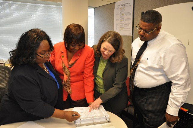 Diane Bennett, (left) chief of the U.S. Army Forces Command Civilian Personnel Branch, reviews Transfer of Function response data with human resources specialists Angela Willis, Marchie Smith and Terry McGee. By April 1, more than 700 FORSCOM employees are to decide whether to move to Fort Bragg, N.C., later this year and next.