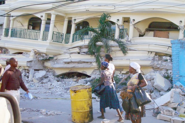 Haitians pass by a government building demolished by the earthquake.