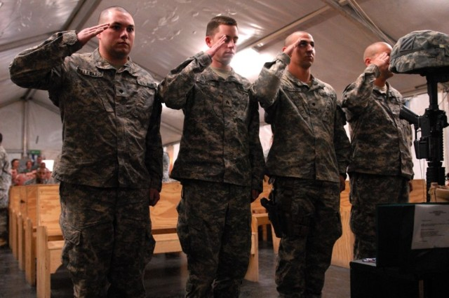 Soldiers assigned to the  2/69 Armor, 3rd HBCT, 3rd ID, render honors during the memorial ceremony for Spc. Michael Snelgrove at Forward Operating Base Kalsu, Feb. 12.