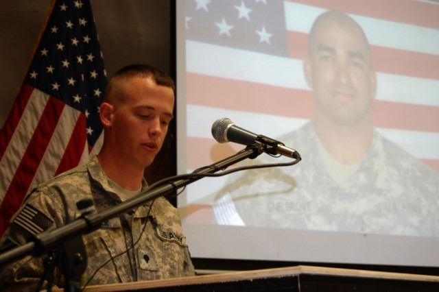 With a picture of Spc. Michael Snelgrove lighting the screen behind him, Spc. James Jenner, a combat medic assigned to HQ Co., 2/69 Armor, 3rd HBCT, 3rd ID, speaks at Snelgrove's memorial ceremony at Forward Operating Base Kalsu, Feb. 12.