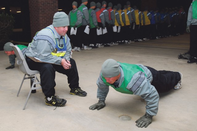 SSG Brett Mahl keeps count as PVT Richard Chmielewski completes as many push-ups as he can in under two minutes during the company's physical fitness test March 8.