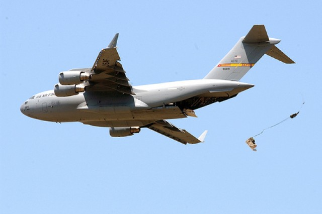 A C-17 Globemaster III releases cargo over a drop zone at Altus Air Force Base. Similars loads of Joint Precision Airdrop System pallets will begin dropping during training missions over the South East Corner range at Fort Sill. The JPADS training begins March 18, and Altus aircrews will fly one or two missions per week. (USAF file photo by Aldric Borders)
