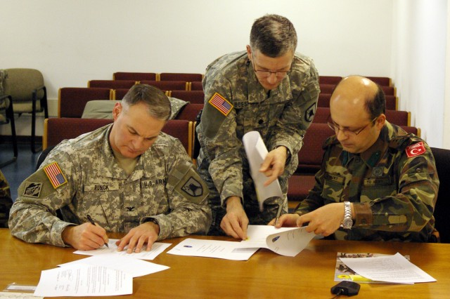 Col. Lannie Runck, left, chief of staff for Multi-National Battle Group-East, and Lt. Col. Ozgur Ozkurt of the Turkish Army, sign documents making Turkey a part of the battle group at a March 9 meeting at Camp Bondsteel. Lt. Col. Scott Boespflug, deputy chief of staff for MNBG-E, assists at the signing.