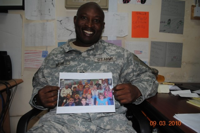 Capt. Otazeria Odibo shows off a photo of students at Skyline and Lincoln Elementary Schools. Students from the Canon City, Colo. schools have corresponded with and sent care packages to Soldiers from the 121st BSB, 4th Brigade Combat Team, 1st Armored Division, deployed to southern Iraq.