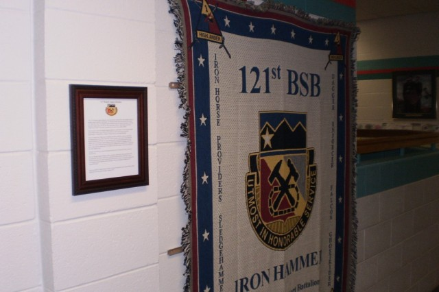 """A commemorative Afghan-style blanket from the 121st Brigade Support Battalion hangs on Skyline and Lincoln Elementary School's """"Wall of Honor.""""  Students from the Canon City, Colo. schools have corresponded with and sent care packages to Soldiers from the 121st BSB, 4th Brigade Combat Team, 1st Armored Division, deployed to southern Iraq."""