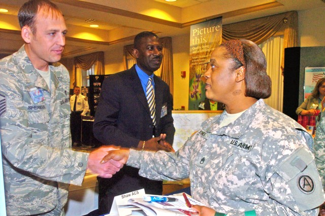 Air Force Master Sgt. John Sherman, Airmen Family Readiness noncommissioned officer in charge at Shaw Air Force Base, greets Staff Sgt. Doretha Jones, chemical, biological, radiological and nuclear NCOIC, Third Army Headquarters and Headquarters Company,  during the expo. Jones attended the expo to learn about the opportunities the Sumter community can offer her Family as she prepares to move with Third Army.