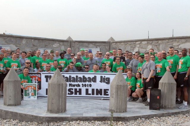 """FOB FENTY, Afghanistan-Servicemembers and civilians serving under Task Force Mountain Warrior group together with the """"Jalalabad Jig"""" banner after running a three-and-a-half mile race in honor of St. Patrick's Day, on Forward Operating Base Fenty in eastern Afghanistan's Nangarhar province, March 13. The race ran as a sister race to the one in Colorado Springs, Colo."""