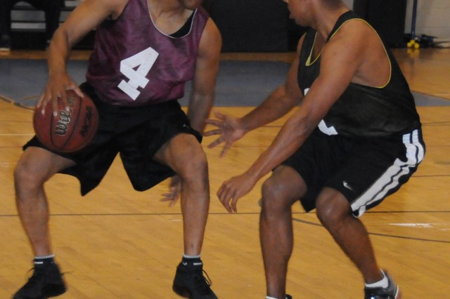 D Co., 1st Bn., 145th Avn. Regt. basketball player Hube Agard tries to dribble past War Eagle Michael Weber during a 67-48 win March 10.