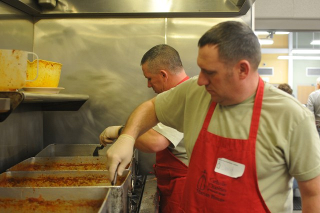 COLORADO SPRINGS, Colo.-Sgt. Kelly Vallery, left, and Staff Sgt. David Burris, right, infantrymen, Company G, 1st Battalion, 67th Armor Regiment, 2nd Brigade Combat Team, 4th Infantry Division, stir pans of Sloppy Joes in preparation for lunch at the Marian House Soup Kitchen March 4.