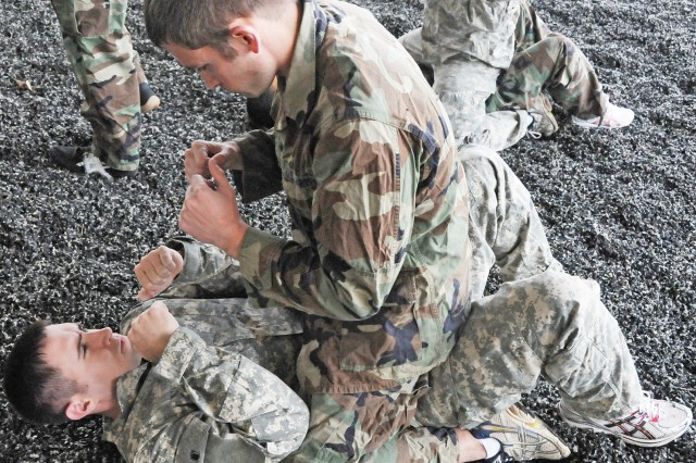 """Capt. Brian Green, bottom, prepares to defend himself from Capt. Matthew Van Epps' """"attack"""" during Modern Army Combatives Program training March 15 at Fort Rucker."""