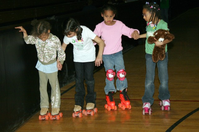 FORT CARSON, Colo.-More experienced skaters help out their friends at Skate Night on Fort Carson.