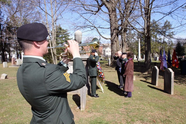 """Sgt. Matthew Belcher from the 78th Army Band plays """"Taps"""" as Mildred T. Trotman, mayor of Princeton Borough (left); Bernard P. Miller, mayor of Princeton Township(right), and Maj. Gen William Monk III, commanding general, 99th Regional Support Command (center) render honors during the Grover Cleveland Presidential Wreath Laying Ceremony at Princeton Cemetery March 18. The White House Military Office is responsible for coordinating the annual placement of Presidential Wreaths at tombs and resting places of former presidents, other famous Americans and at certain memorials of historical significance.  (Photo by 0 Staff Sgt. Alyn-Michael MacLeod)"""