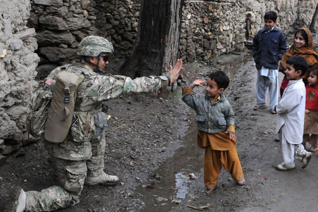 KUNAR PROVINCE, Afghanistan - A child from the Angla Kala village in eastern Afghanistan's Kunar province, gives a high five to U.S. Army Spc. Jesus B. Fernandez, of San Jose, Calif., an assistant team leader with 3rd Platoon, Company C, 2nd Battalion, 12th Infantry Regiment, Task Force Lethal, during a unit visit, Feb. 6. International Security Assistance Force troops regularly meet with village elders to improve communications between residents and government officials. (Photo by U.S. Army Staff Sgt. Gary A. Witte, 300th Mobile Public Affairs Detachment)