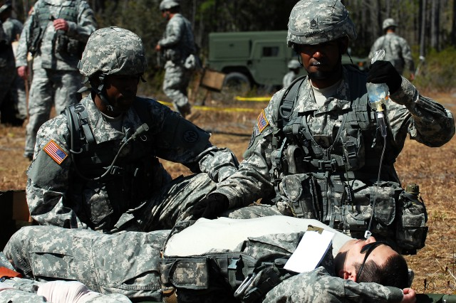CAMP BLANDING, FLA-- New York Army National Guard Staff Sgt. Onix Lugo, a member of Target Acquisition Platoon Sergeant for Headquarters and Headquarters Battery, 1st Battalion, 258th Field Artillery Regiment, holds an IV bag for a simulated casualty during his unit's mass casualty exercise at Camp Blanding, Florida, March 13.