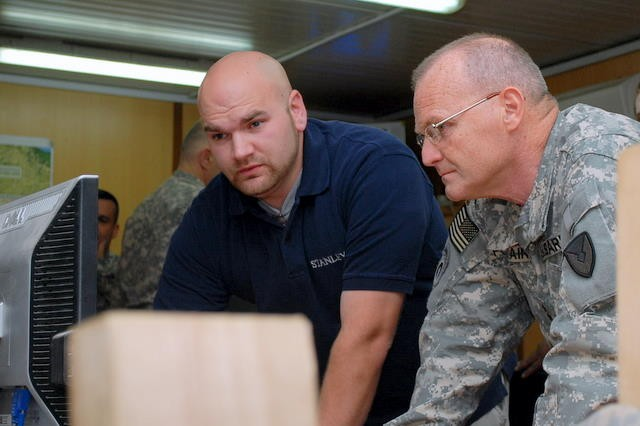 Adam Coffman explains the SDS database to Maj. Gen. Yves J. Fontaine, commanding general, Army Sustainment Command, at Joint Base Balad, Iraq.
