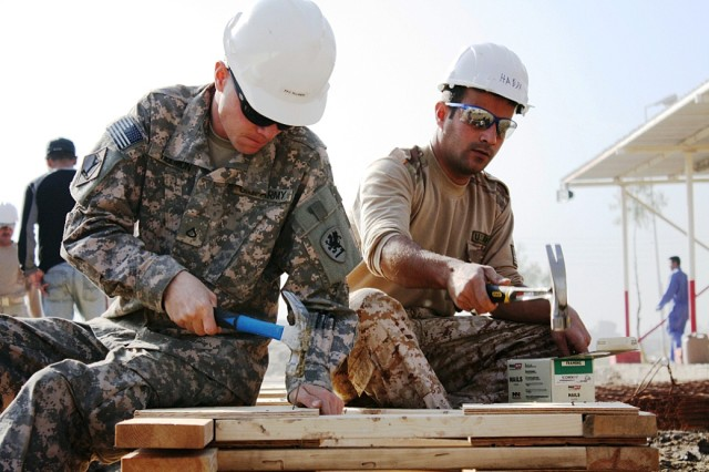 A U.S. and Iraqi Soldier work side-by-side during the construction of the Joint Operation Center on Forward Operating base Constitution.