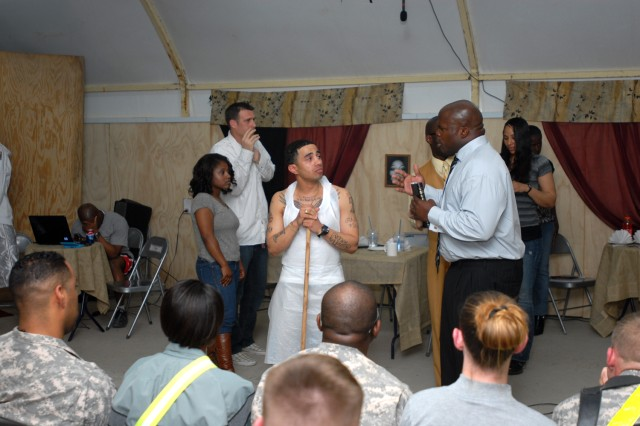 "Pastor Waters (right), played by Staff Sgt. Altierre Q. Bell 14th Border Transition Team, counsels Roderick (left), played by Staff Sgt. Jose Rios, Division Headquarters and Headquarters Battalion, 1st Infantry Division, a Philadelphia native, during a pause in which the other characters on the stage are frozen in place, interrupting a moment of questioning his life by Roderick to remind him anything can be turned around through faith, during the Basra Gospel Choir's performance of ""Fannie Mae's Café,"" at the Contingency Operating Base Basra Town Hall, March 19, 2010."