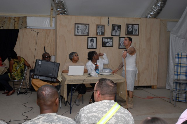 "Roderick (far right), played by Staff Sgt. Jose Rios, Division Headquarters and Headquarters Battalion, 1st Infantry Division, a Philadelphia native, is told his input isn't wanted by Samantha, played by 1st Lt. Shamika Hill, 367th Mobile Public Affairs Detachment, a Columbus, Ohio native, while Fannie Mae, Samantha's mother, played by Maniececia Peterson, 256th Signal Company, 17th Fires Brigade, a Memphis, Tenn. native, discusses a business proposal with Samantha and Mr. Raphaellosso (left), played by Spc. Andrez Powell, 1st Attack Reconnaissance Battalion, 130th Aviation Regiment, a Raleigh N.C. native, during the Basra Gospel Choir's performance of ""Fannie Mae's Café,"" at the Contingency Operating Base Basra Town Hall, March 19, 2010."