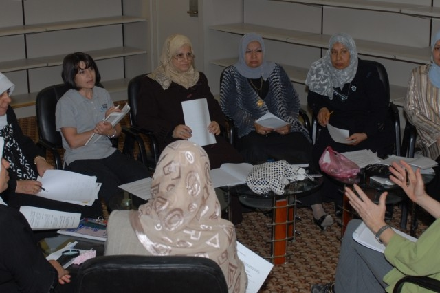 Margaret Ostrenko, a social scientist with the Army's Human Terrain System, explains a cultural concept to employees at Basra International Airport during an English class at the airport, March 14, 2010.
